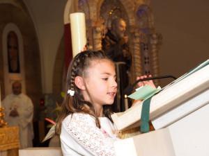 Una bimba legge la preghiera dei fedeli